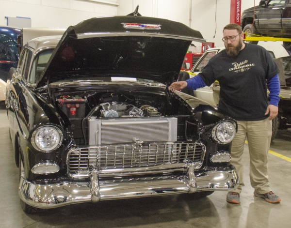Lead judge Gabe Winger, diesel technology instructor, points to the motor of a 1955 Chevy Bel Air as he explains what the judges are looking for at the ninth annual Vehicle Extravaganza at Salina Area Technical College on Saturday. This was Winger's last year as judge of the show. [AARON ANDERS / SALINA JOURNAL]