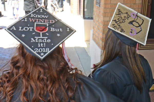 Graduates Tamre Petree and Vonetta Robinson, of Salina Area Technical College, wear the graduation caps they decorated outside the Stiefel Theatre before commencement on Saturday. [AARON ANDERS / SALINA JOURNAL]