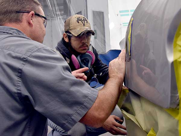 Teacher and student inspecting auto body work