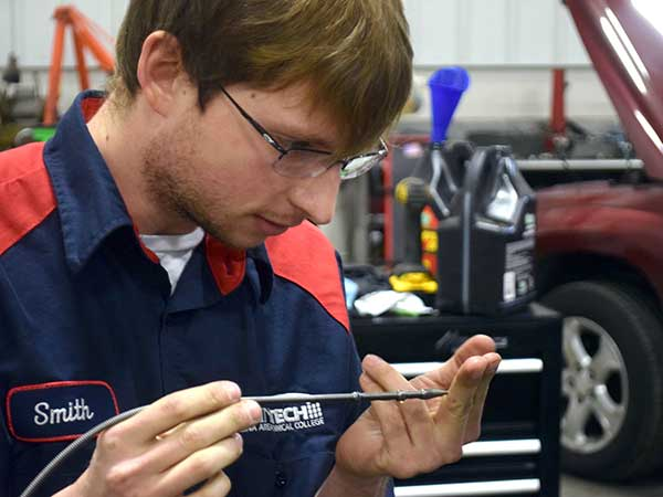 Auto Tech student looks at oil on a dipstick