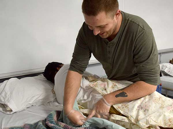 CNA student learns to make a bed with patient in it