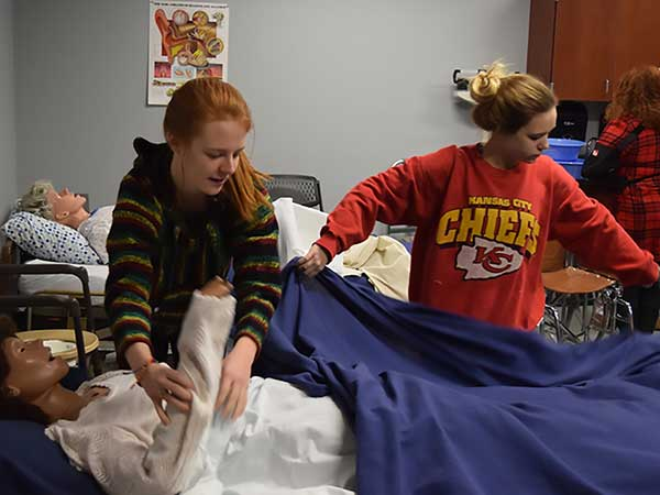 CNA students learn to make a bed with patient in it