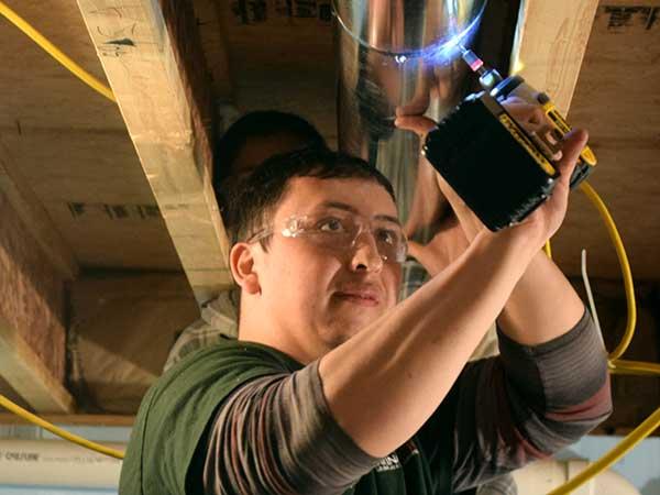 HVAC slideshow -- student installing ductwork
