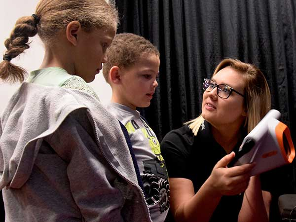 Medical Assistant student shows children how a vision test works