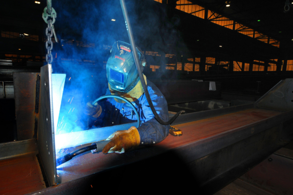 A welder at PKM Steel works on a steel beam [Tom Dorsey / Salina Journal]