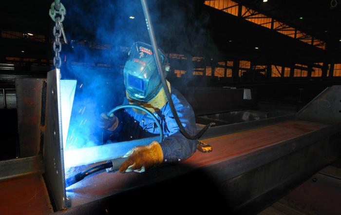A welder at PKM Steel works on a steel beam [Tom Dorsey / Salina Journal]